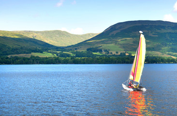 sailboat on a Scottish lake, beautiful hills in background