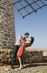 man and woman dancing near a windmill