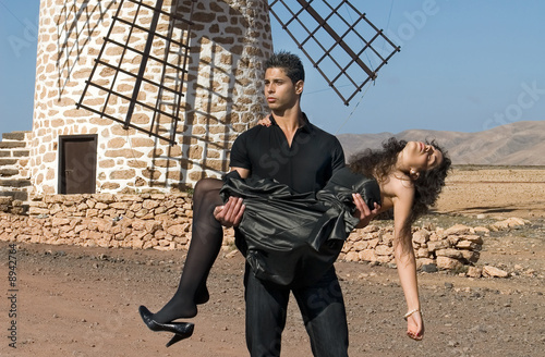 muscled man in black with a woman in arms