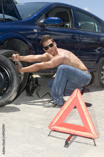 man changing a broken wheel of his car