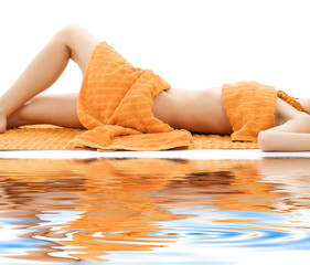 torso of relaxed lady with orange towels on white sand