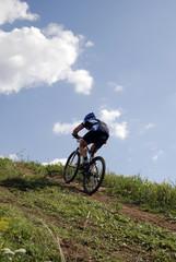 Bicyclist on a background blue sky