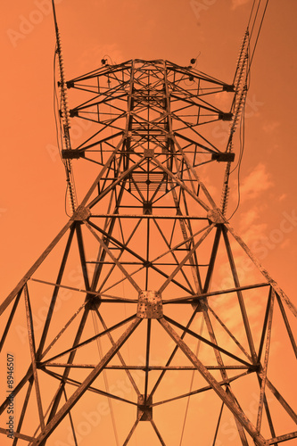 Power transmission pole against sunset skies