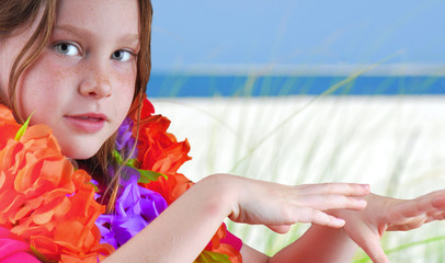 Young girl doing hula dance on gorgeous beach