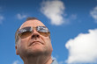 Man wearing sun glasses against the blue sky.