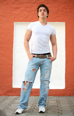 portrait of the young man in blue jeans near red wall