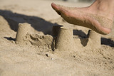 A sand castle at the beach about to be destroyed by a foot poster