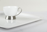 White porcelain cup on white plate poster