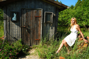 blond woman in white dress sitting near wood hut