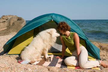 Girl with dog sitting near of a tent at seaside