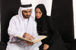Постер, плакат: Arab Man Reads & Explains Verses From The Quran To His Wife