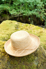 Straw raffia Hat on rock by river