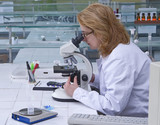 Female researcher looking through microscope poster