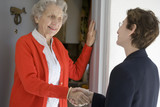 Attractive senior woman shaking hands with visitor poster