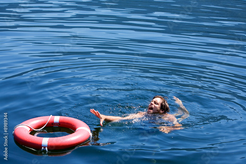 A man struggling for a life buoy in the water