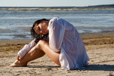 Dreamy young woman sitting on a beach poster