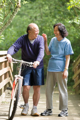 A couple senior asian talking and exercising at a park
