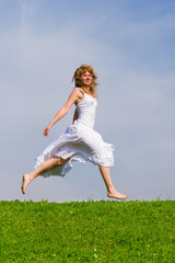 Girl runs on a grass on a background of the blue sky