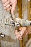 Closeup of plumbers hands using crescent wrenches poster