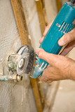 Closeup of a plumbers hands using a grinder on water pipe poster