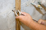 Closeup of a plumbers hands tightening a nut on a water pipe poster
