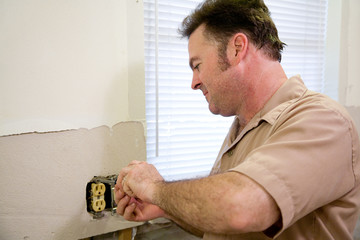 Electrician repairing an electrical outlet.