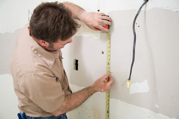 Contractor measuring and marking the drywall