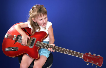 little girl playing with red electric guitar and singing