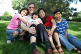 Large multiracial family sitting on lawn poster