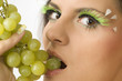 close up of a sensual girl with green eyelashes and grape