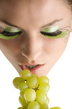 close up of a young girl and beautiful girl with grape near
