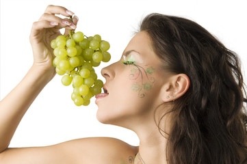 sensual brunette with leaf painted on face licking green grape