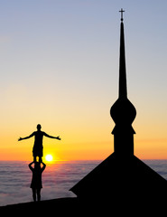 acrobatic couple practicing in sunset beside a church