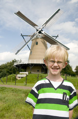 Little boy is in Holland in front of a Dutch windmill