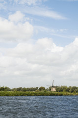 windmill in Dutch landscape with river in front