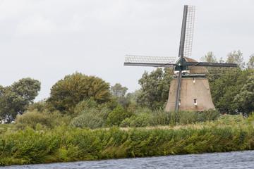 Windmill in Dutch landscape near the river
