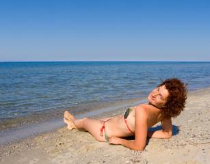 Girl lie at sea coast and looking to camera
