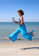 Girl with laptop running along sea beach