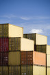 shipping freight containers stacked in port against blue sky