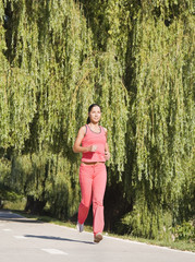 Young woman running in a park near a drooping willow tree.