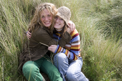 Young women hugging each other in grass