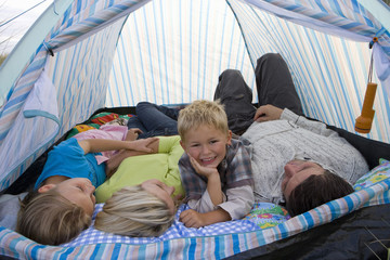 Young family lying in tent