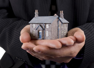 Real estate concept, businessman holding model house