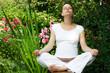 Young pregnant woman meditating at summer garden