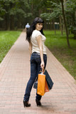 young smiling brunet girl with shopping bags outdoor poster