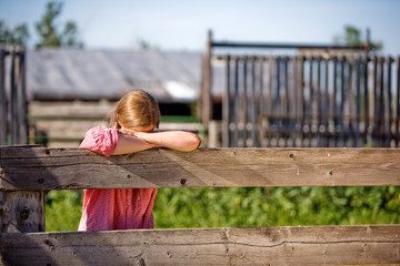 A farm girl resting on the fence