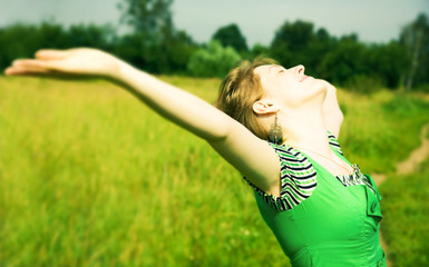 Young happy woman delighting good weather. Soft green tint.