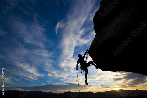 Rock climber dangling from a cliff.