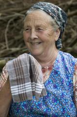 Alte Bäuerin mit Stofftaschentuch lacht