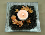 Tea candle set on stones with native seed pods. poster